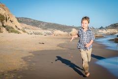 跑在海滩的小男孩 库存照片