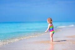 跑在海滩的小逗人喜爱的女孩 免版税库存图片