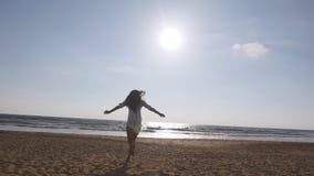 跑在海滩的少妇到海洋在日落和被举的手 去在含沙岸的美丽的女孩 影视素材