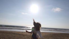 跑在海滩的少妇到海洋在日落和被举的手 去在含沙岸的美丽的女孩 股票录像