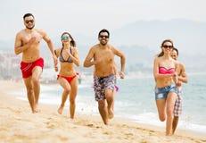跑在海滩的愉快的人民 免版税库存照片