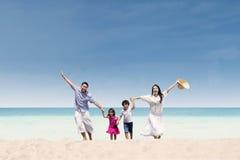 跑在海滩的愉快的家庭 免版税库存照片