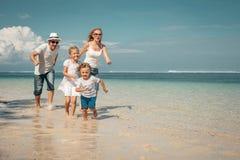 跑在海滩的愉快的家庭 免版税库存图片