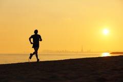 跑在海滩的慢跑者剪影在日落 免版税库存照片