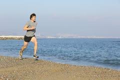 跑在海滩的慢跑者在水附近 免版税图库摄影