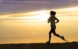 跑在海滩的日落的运动员 库存照片