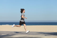 跑在海滩的沿海岸区的一个人的侧视图 库存照片