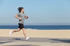 跑在海滩的沿海岸区的运动员 库存图片