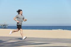 跑在海滩的沿海岸区的年轻运动员 免版税库存图片