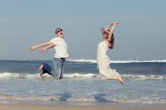 跑在海滩的爱恋的夫妇在天时间 库存图片