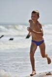 跑在海滩的男孩 免版税库存照片