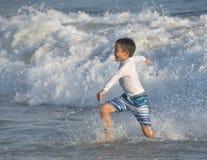 跑在海洋的男孩 免版税库存照片