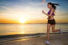 跑在海滩的美好的日落的妇女 免版税库存照片