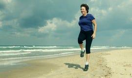 跑在海滩的资深妇女 免版税图库摄影