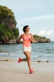 跑在海滩的运动的妇女 图库摄影
