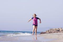 跑在海滩的逗人喜爱的小女孩 免版税图库摄影