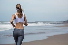 跑在海滩的年轻亭亭玉立的妇女 回到视图 库存图片