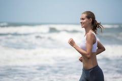 跑在海滩的年轻亭亭玉立的妇女 免版税图库摄影