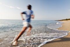 跑在海滩的年轻人。 库存图片