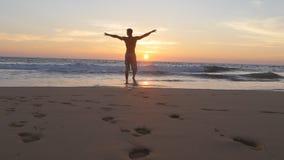 跑在海滩的年轻人到海洋在日落和被举的手 去在含沙岸的运动的人海在期间 股票视频
