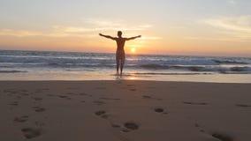 跑在海滩的年轻人到海洋在日落和被举的手 去在含沙岸的运动的人海在期间 免版税库存图片