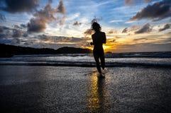 跑在海滩的年轻人,当日落 库存图片