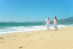 跑在海滩的年轻浪漫夫妇握手 库存照片