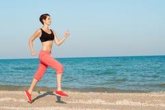 跑在海滩的年轻美丽的女子运动员 库存照片