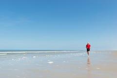 跑在海滩的更老的人 免版税库存照片