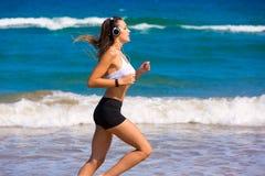 跑在海滩耳机的深色的女孩 免版税库存图片