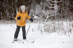 跑在滑雪的年轻欧洲女孩在冬天森林,全长,复制空间 免版税库存图片