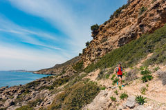 跑在激动人心的山和海边的人 免版税库存图片