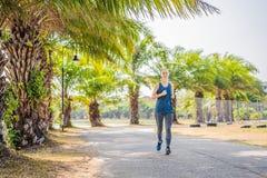 跑在热带公园的赛跑者运动员 妇女健身日出跑步的锻炼健康概念 免版税库存图片