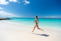 跑在热带海滩的少妇 库存图片