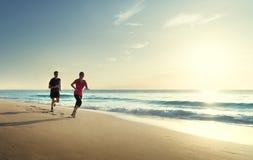跑在热带海滩的男人和妇女 免版税库存图片