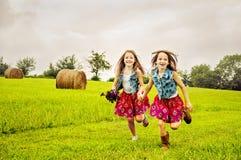 跑在牧场地的女孩兄弟姐妹 免版税库存照片
