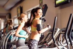 跑在现代健身房的踏车的两名适合的妇女 库存图片