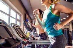 跑在现代健身房的踏车的两名适合的妇女 免版税图库摄影