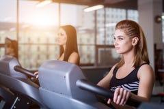 跑在现代健身房的踏车的性感的适合妇女 做在踏车的健康女孩连续锻炼在健身房 免版税库存照片