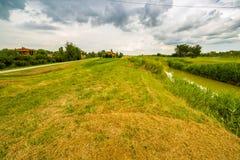 跑在田园大局的18世纪教会附近的河 库存照片