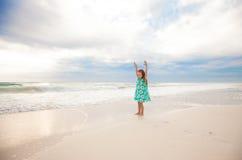 跑在白色沙滩的小逗人喜爱的女孩 免版税库存照片