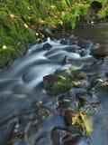 跑在石渣和石头的小河被弄脏的蓝色波浪。  免版税图库摄影