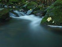 跑在石渣和石头的小河被弄脏的蓝色波浪。  库存图片