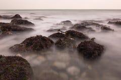 跑在石头之间的海水在海洋 免版税库存照片