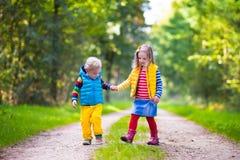 跑在秋天公园的孩子 免版税库存图片
