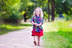 跑在秋天公园的小女孩 免版税库存照片