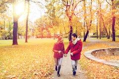 跑在秋天公园的愉快的年轻夫妇 库存照片