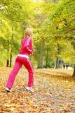 跑在秋天森林里的妇女。女性赛跑者训练。 库存图片