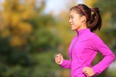 跑在秋天的秋天森林里的亚裔妇女 图库摄影