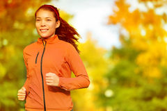 跑在秋天秋天森林里的赛跑者妇女 免版税库存照片